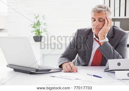 Tired businessman falling asleep at desk in his office poster