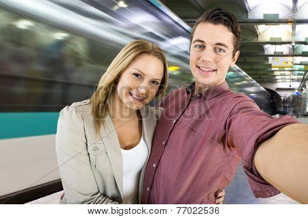 Young couple taking a selfie while waiting for their train to arrive