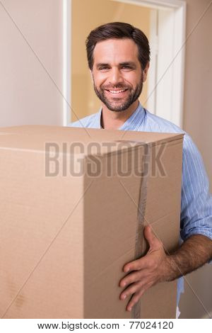 Happy man carrying moving box in his new home