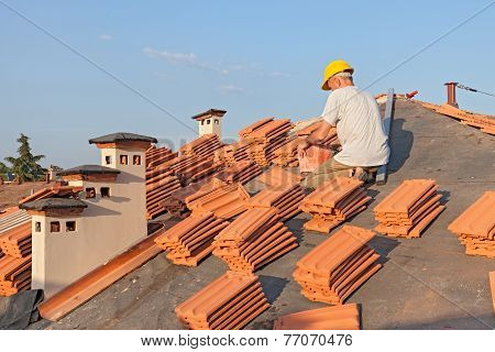 roofing: construction worker on a roof covering it with tiles - roof renovation: installation of tar paper, new tiles and chimney poster