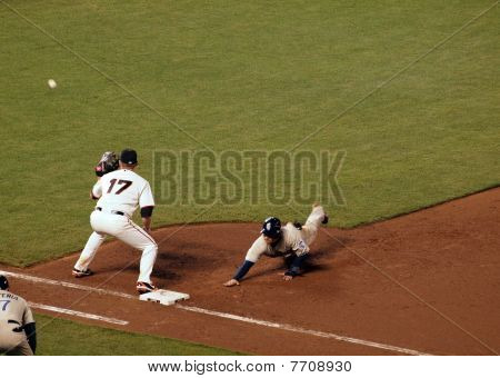 Giants First Baseman Gets Ready To Catch A Ball As A Padre Baserunners Slides Head First Back To Fir