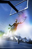 A basketball player drives to the hoop for a slam dunk with abstract rainbow lens flare and halftone effects. poster