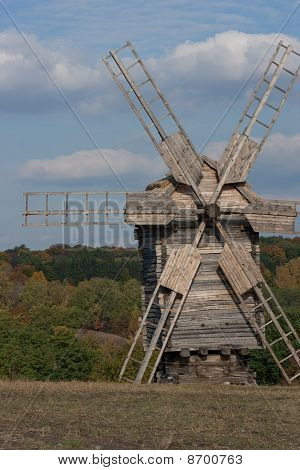 Wooden Windmill. Autumnal Forest In The Background.
