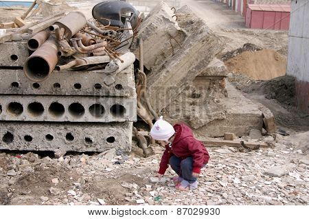 The little girl lifts a stone fragment