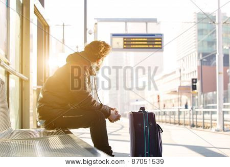 Young Man Sitting At Train Station Looking At Time Schedule