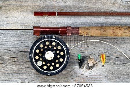 Antique fly fishing reel and rod on rustic wood. Layout in horizontal format. poster