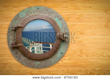 Antique Porthole On Bamboo Wall With View Of Ship Deck Railing And Ocean