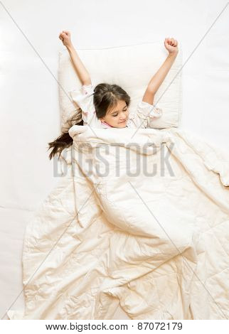 Isolated Shot Of Cute Girl Being Awake And Stretching In Bed
