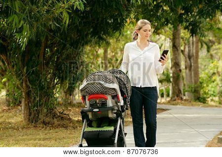 Mother With Baby In Pushchair Typing Message On Phone