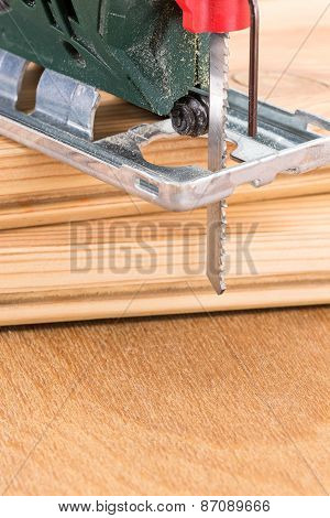 Green Fretsaw On Wooden Plank