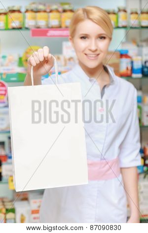 Pharmacist stretches out the paper bag