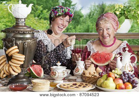 Two Cheerful Women Drinking Tea Outdoors