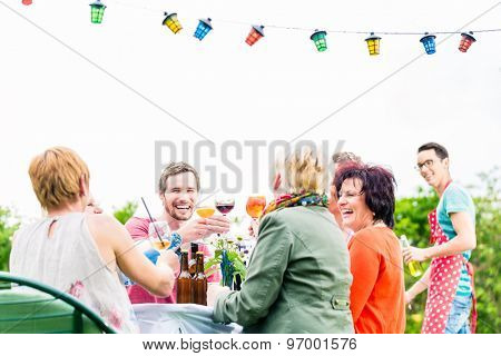 Friends and neighbors on long table celebrating party toasting with drinks