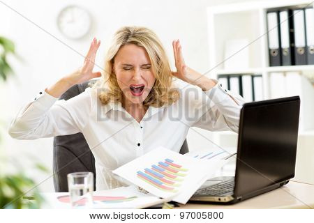 Stressed businesswoman at laptop in office