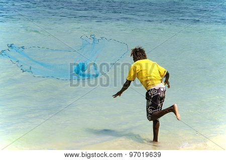 Young Mauritian Man On The Beach  Throws Out A Net To Fish