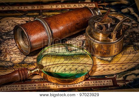 Travel geography navigation concept background - old vintage retro compass with sundial, spyglass and magnifying glass on ancient world map poster