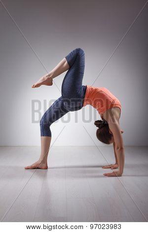 Beautiful sporty fit yogini woman practices yoga asana eka pada chakrasana (or eka pada urdva dhanurasana)  - one-legged wheel pose (or one-legged upward facing bow) pose in studio