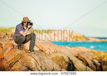 Young photographer taking photos at the beach