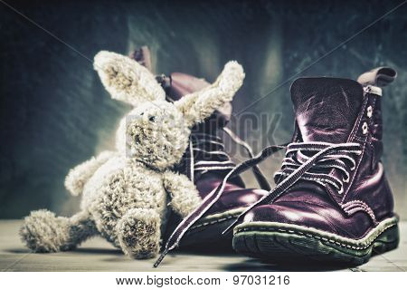 Baby boots and plush rabbit toy close up shot. Grungy backgrounds