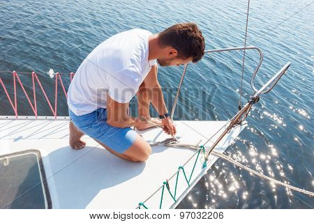 Positive man adjusting his yacht