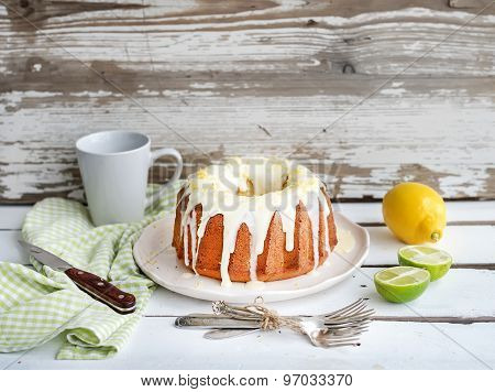Moist lime and lemon bundt yoghurt cake, white rustic wooden  background.