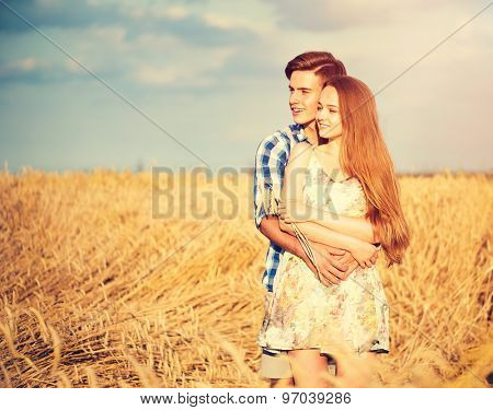 Beauty Couple relaxing on wheat field together. Happy girlfriend and boyfriend having fun outdoors, kissing and hugging, first love concept. Beautiful Boy and Girl in love together