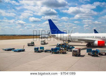 Airplanes and luggage cars on an airport