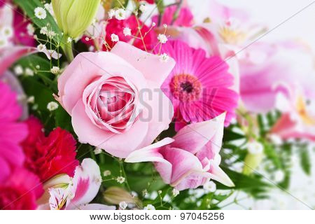 Pinkish tone flower bouquet, with focus on light pink rose. shallow depth of field. high key.