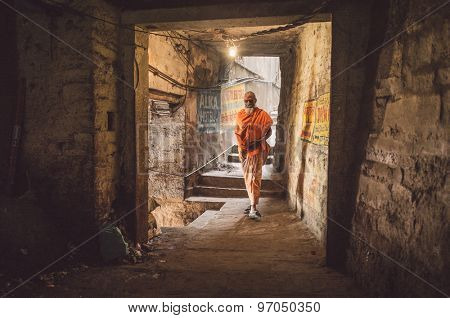 VARANASI, INDIA - 20 FEBRUARY 2015: A sadhu walks through a passage.  In Hinduism, a sadhu is a religious ascetic or holy person. Post-processed with grain, texture and colour effect.
