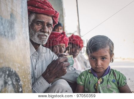 GODWAR REGION, INDIA - 12 FEBRUARY 2015: Rabari tribesman with other members while granddaughter stands next to him. Post-processed with grain, texture and colour effect.