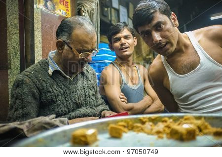 JODHPUR, INDIA - 07 FEBRUARY 2015: Candy store owner next to two workers finishing full day shift. Workers around India are mostly underpaid and overworked.
