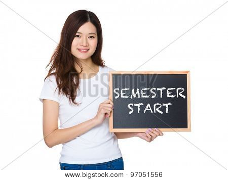 Woman with the chalkboard showing phrase of semester start