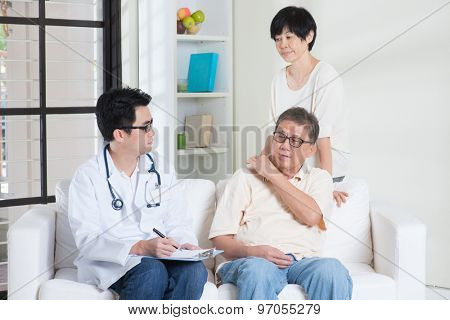 Doctor and patient. Asian old people consult family doctor, sitting on sofa. Senior retiree indoors living lifestyle.