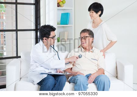 Doctor and patient. Sick Asian old man consult family doctor, sitting on sofa. Senior retiree indoors living lifestyle.