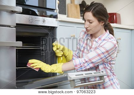 Fed Up Woman Cleaning Oven At Home