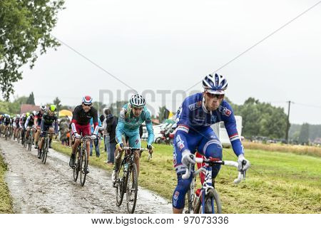 The Peloton On A Cobbled Road- Tour De France 2014
