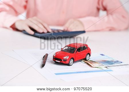 Toy car and documents on table. Car insurance concept