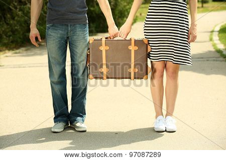 Young couple holding vintage suitcase outdoors