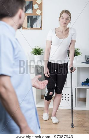 Young woman using crutch after knee injury poster