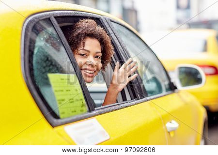 business trip, transportation, travel, gesture and people concept - young smiling african american woman driving in taxi and waving hand at city street