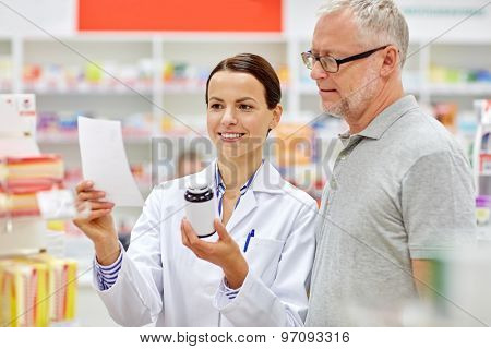 medicine, pharmaceutics, health care and people concept - happy pharmacist and senior man customer with drug and prescription at drugstore