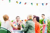 Friends and neighbors on long table celebrating party toasting with drinks poster