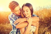 Beauty Couple relaxing on wheat field together. Happy girlfriend and boyfriend having fun outdoors, kissing and hugging, love concept. Beautiful Boy and Girl in love together poster