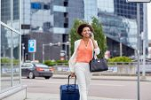 travel, business trip, people and technology concept - happy young african american woman with travel bag walking down city street and calling on smartphone poster
