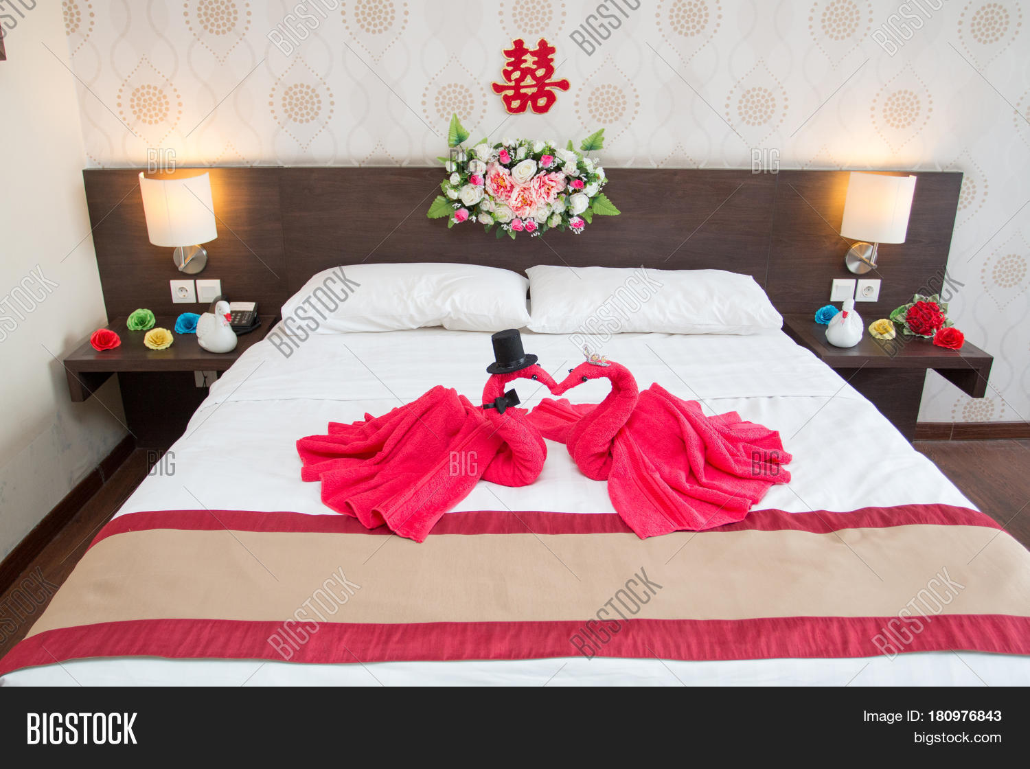 Two Swans Made Of Towels Forming Heart Shape On Bed In Honeymoon Suite Room Hotel Decorated