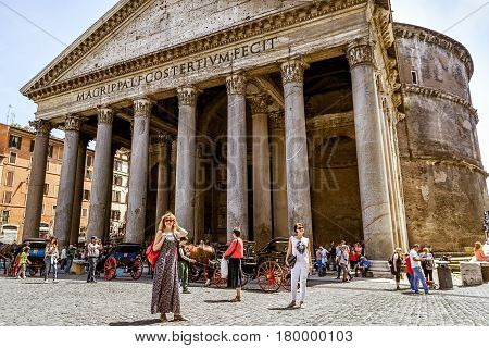 ROME, ITALY - MAY 9, 2014: Tourists visit the Pantheon at the Piazza della Rotonda. Pantheon is a famous monument of ancient Roman culture the temple of all the gods built in the 2nd century.