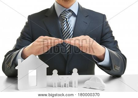 Insurance concept. Male hands covering toy house, family and car on table