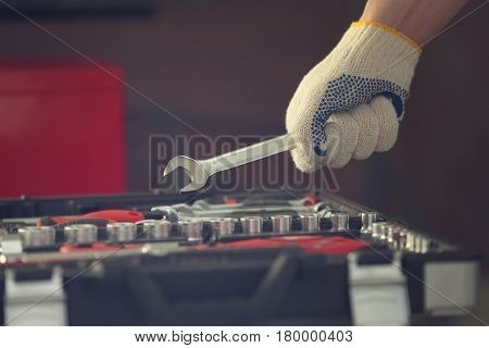 Auto mechanic selecting tools in car repair shop, closeup