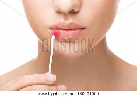 Young woman with cotton swab near face, closeup. Herpes virus concept