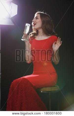 Happy charming young woman in red dress sitting and drinking champagne over black background